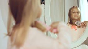 Moderne kleine Dame, die ihr Haar kämmt und im Spiegel schaut Lizenzfreies Stockfoto