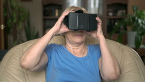Moderne knappe hogere vrouwenzitting op gele stoel die thuis virtuele werkelijkheidsglazen gebruiken stock footage