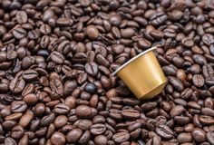 Moderne koffiecapsule op de geroosterde koffieboon stock foto's