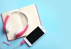 Moderne Kopfhörer, Telefon und offenes Notizbuch auf Farbhintergrund, flache Lage stockbild