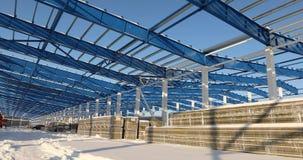 Moderne LagerhausBaustelle, die Baustahlstruktur eines neuen Handelsgebäudes gegen ein klares Blau stock footage
