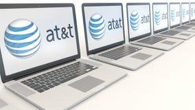 Moderne Laptops mit American Telefone und Telegraf Company AN t-Logo Computertechnologie-Begriffsleitartikel 3D Lizenzfreie Stockfotos