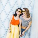 Moderne Mädchen der schönen jungen Paare blond und Brunette in einem hellen gelben Kleid und in Sonnenbrille, die für den Ca aufw Stockfoto