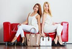 Moderne Mädchen mit Taschenhandtaschen auf roter Couch lizenzfreie stockbilder