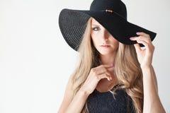 Moderne Mädchenblondine mit blauen Augen in einem Hut mit einem Rand Lizenzfreies Stockbild