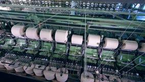 Moderne machines die draden in een faciliteitenruimte spoelen Industriële textielfabriek stock footage