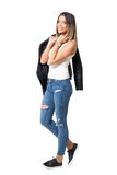 Moderne mannequin die jeans, mouwloos onderhemd, leerjasje en tennisschoenen dragen die bij camera stellen royalty-vrije stock fotografie