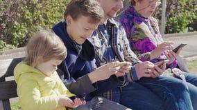 Moderne mededeling: familie met mobiele telefoons openlucht, dag stock video