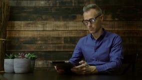 Moderne mens die een tablet in een koffie gebruiken stock videobeelden