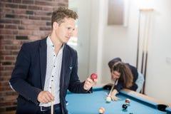 Moderne mens met poolbal die zich naast snookerlijst bevinden stock foto