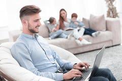 Moderne mensen werkende laptop in zijn woonkamer stock afbeelding