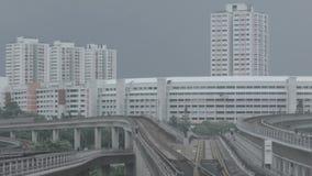 Moderne metro op een spoorweg in Sinapore op een achtergrond van stadsgebouwen schot MRT van de de massa snelle trein van Singapo stock videobeelden
