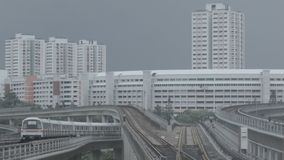 Moderne metro op een spoorweg in Sinapore op een achtergrond van stadsgebouwen schot MRT van de de massa snelle trein van Singapo stock afbeelding