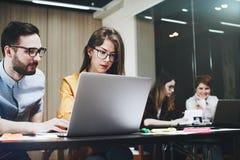 Moderne Mitarbeiter der Gruppe, die während des Arbeitsprozesses sich besprechen Stockbild