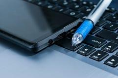 Moderne mobiele telefoon, blauwe ballpoint op laptop Royalty-vrije Stock Afbeelding