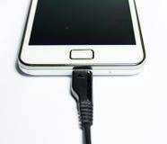 Moderne mobiele telefoon op last Op een witte achtergrond royalty-vrije stock afbeeldingen