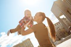 Moderne moderne Mutter auf einer städtischen Straße mit einem Pram. Junges m Stockfotos