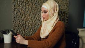 Moderne moslimvrouw in hijab in caffe Arabische smartphone van het vrouwengebruik stock videobeelden