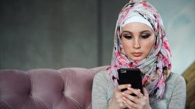 Moderne moslimvrouw met smartphone Concept moderne heldere kleurrijke hijab stock videobeelden