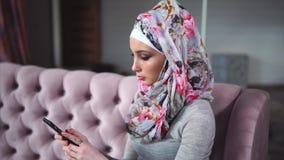 Moderne moslimvrouw met smartphone Concept moderne heldere kleurrijke hijab stock footage