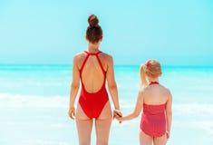 Moderne Mutter- und Tochterstellung auf Seeküste lizenzfreie stockfotografie