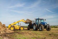 Moderne Nieuwe de tractortractor die van Holland omhoog met mest voor mest het uitspreiden worden geladen royalty-vrije stock afbeelding