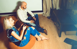 Moderne Paare in der zufälligen Kleidung, die Spaß hat und Computer spielt Stockfoto