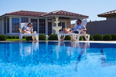 Moderne Paare, die Sonnenbräune unter der Sonne nahe Pool erhalten stockfoto