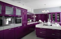 Moderne purpurrote Küche mit stilvollen Möbeln stockfotos