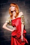 Moderne red-haired Frau in einem roten Kleid des Satins Stockfotos