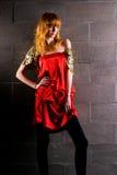 Moderne red-haired Frau in einem roten Kleid des Satins Lizenzfreies Stockfoto