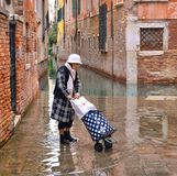 Moderne reife Frau Trandy mit Gamaschen, Stiefeln und Koffer an der Flut in der alten schmalen überschwemmten Straße stockfotografie