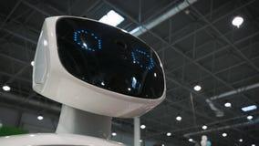 Moderne robotachtige technologieën De robot bekijkt de camera bij de persoon De robot toont emoties stock footage