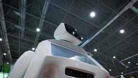 Moderne robotachtige technologieën De robot bekijkt de camera bij de persoon De robot toont emoties stock video