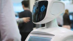 Moderne robotachtige technologieën De robot bekijkt de camera bij de persoon De robot toont emoties stock videobeelden