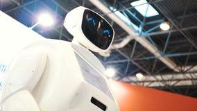 Moderne robotachtige technologieën De robot bekijkt de camera bij de persoon De robot toont emoties Heft omhoog zijn handen op stock videobeelden