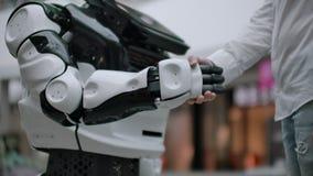Moderne robotachtige technologie?n Een mens communiceert met een robot, drukt een plastic mechanisch wapen aan de robot, handdruk stock videobeelden