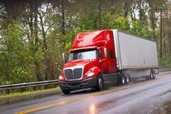 Moderne rode glanzend in aanhangwagen van de regen de semi vrachtwagen op regenende weg