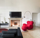 Moderne rode leunstoel in woonkamer Stock Afbeeldingen
