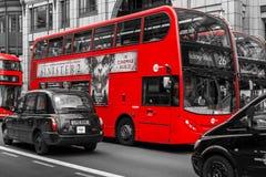 Moderne rote Busse und schwarze Fahrerhäuser in London Bishopsgate Stockbilder