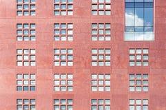 Moderne rote Steinwand mit vielen Fenstern Stockfoto