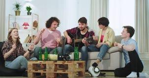 In moderne ruime woonkamer geniet een groep vrienden samen van de tijd op bank het spelen op gitaar het zingen en stock videobeelden