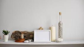 Moderne ruimtedecoratie met Omlijstingmodel Plank tegen witte muur met decoratieve kaars, glas en rotsen Hand die D zetten stock video