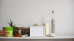 Moderne ruimtedecoratie met Omlijstingmodel Plank tegen witte muur met decoratieve kaars, glas en rotsen Hand die D zetten stock footage