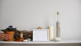 Moderne ruimtedecoratie met Omlijstingmodel Plank tegen witte muur met decoratieve kaars, glas en rotsen Hand die D zetten stock videobeelden