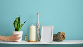 Moderne ruimtedecoratie met Omlijstingmodel Witte plank tegen pastelkleur turkooise muur met Kaars en rotsen in fles Hand stock video