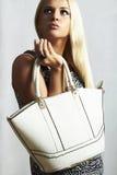 Moderne schöne blonde Frau mit Handtasche. Stockfotografie