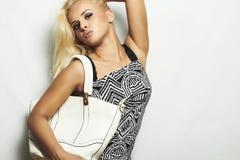 Moderne schöne blonde Frau mit Handtasche Lizenzfreies Stockbild