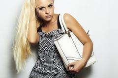 Moderne schöne blonde Frau mit Handtasche Stockfotos