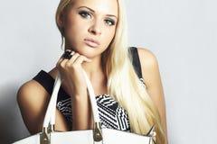 Moderne schöne blonde Frau mit mit Handtasche. Einkauf Lizenzfreies Stockbild